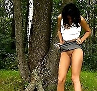 Sexy brunette teen peeing in the country park