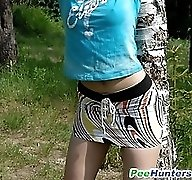 Teen kitty with wavy blonde hair tinkles in forest
