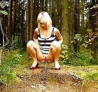 Young blonde with a lot of tattoos pisses in woods