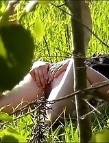 Sunbathing girl in a meadow plays with her slit